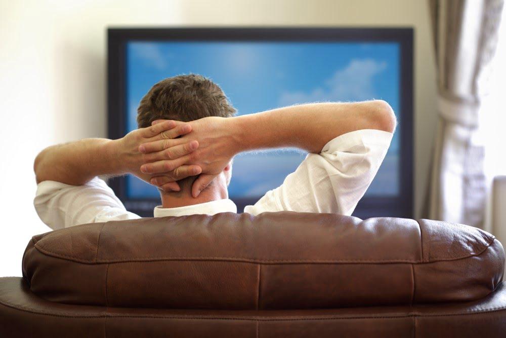 Mand der sidder i sofaen foran sit TV