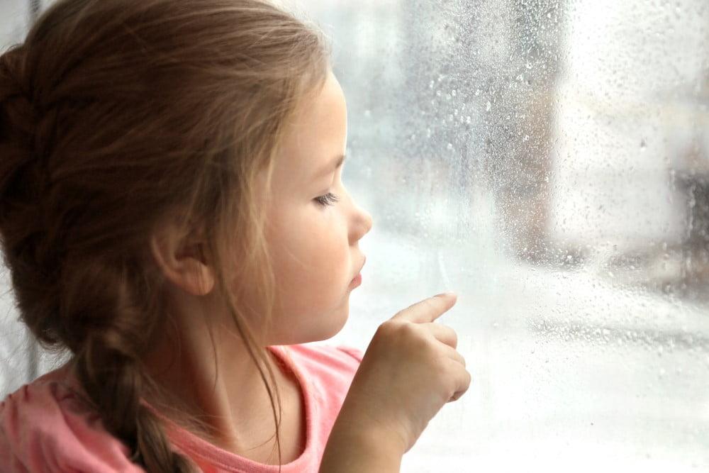 Pige foran regnvåd vindue
